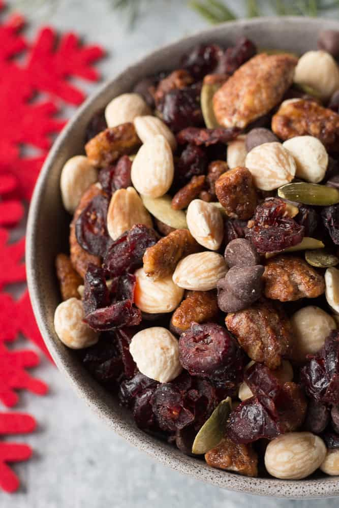 close up of holiday trail mix in a gray bowl with red and green accents surrounding it