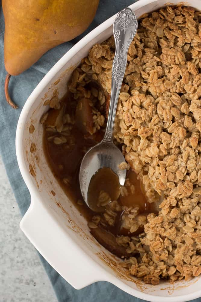 top down shot of pear crisp in a white dish with a spoon and a pear on the side
