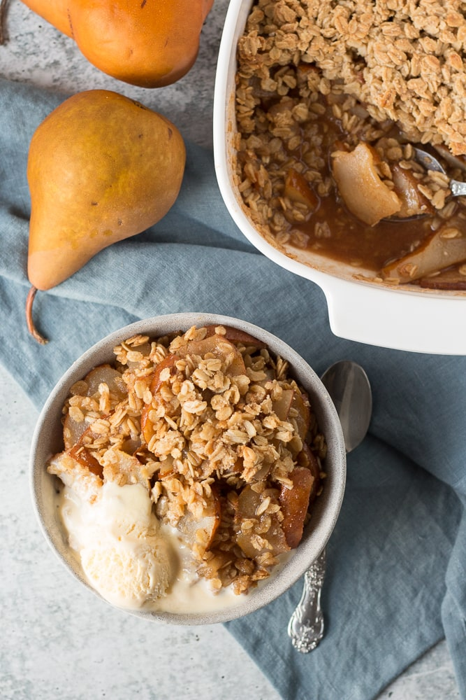 pear crisp in a bowl with vanilla ice cream, next to a baking dish, blue towel, and whole pears
