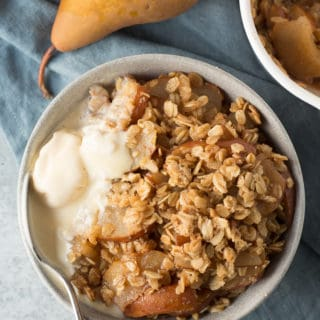 bowl of gluten free pear crisp with melted ice cream and a spoon