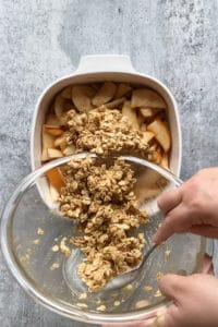 spooning oat topping over cooked pears in a square white baking dish