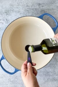 measuring out oil over a pot