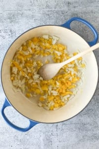 diced onion and bell pepper in a pot with a wooden spoon
