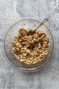 mixed together topping for pear crisp in a clear bowl, with a spoon