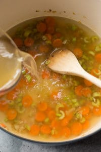 pouring turkey stock into a large pot with cut veggies in it.
