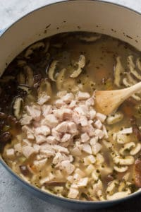 chopped turkey added into a pot for turkey and rice soup