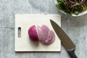 red onion thinly sliced on a cutting board