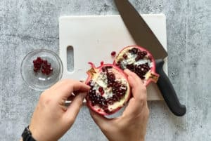 hands picking out pomegranate seeds from a pomegranate over a cutting board