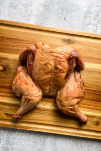 a smoked whole chicken resting on a cutting board