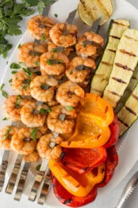 grilled shrimp skewers with bell peppers and zucchini on a white platter