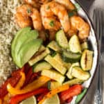 top down shot of a grilled shrimp bowl with veggies and cauliflower rice