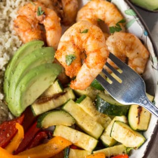 a fork holding a piece of grilled shrimp over a bowl of grilled veggies and shrimp