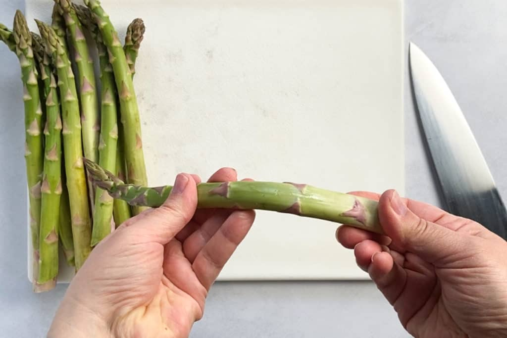 two hands bending a spear of asparagus