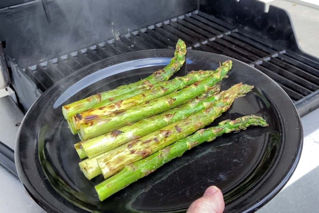 freshly grilled asparagus removed from the grill on a black plate