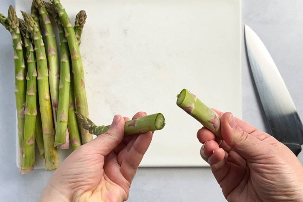 two hands holding a snapped asparagus spear