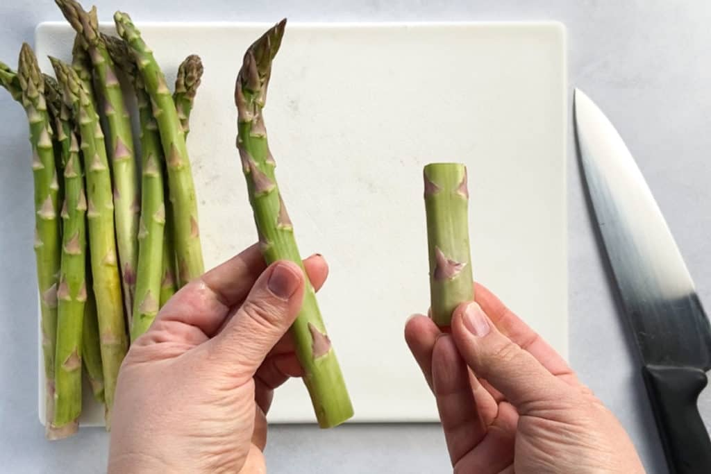 hands holding the top and bottom of a snapped asparagus stalk