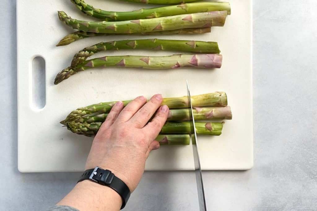 cutting the ends off a row of asparagus