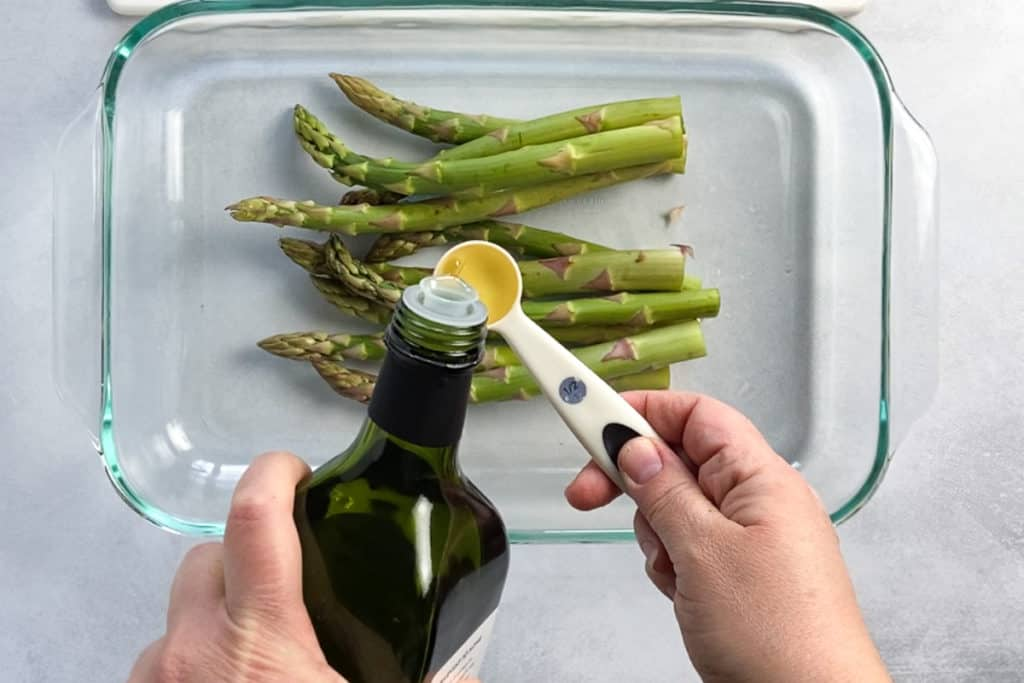 pouring oil into a measuring spoon for the asparagus