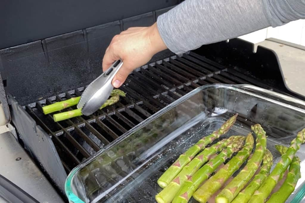 placing asparagus on a grill