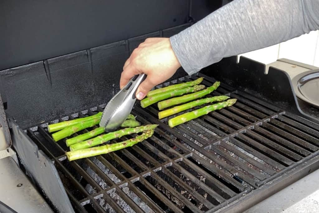 flipping grilled asparagus on the grill grates
