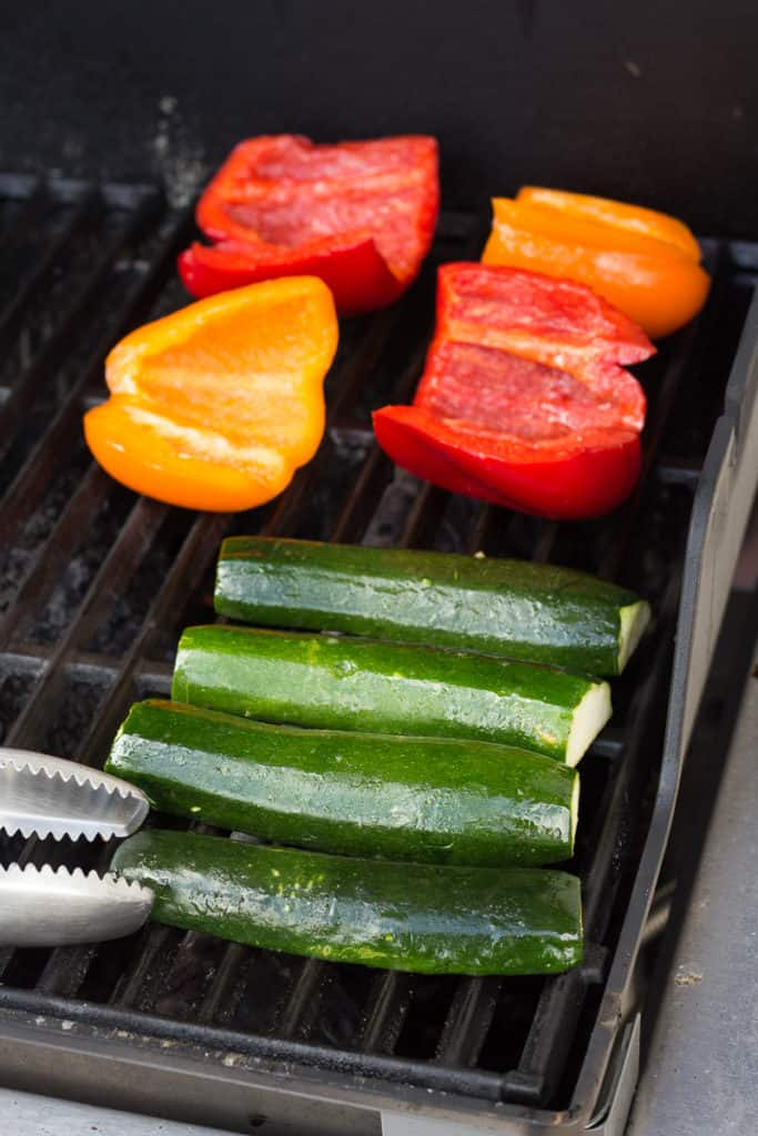 placing cut bell pepper and zucchini on a grill
