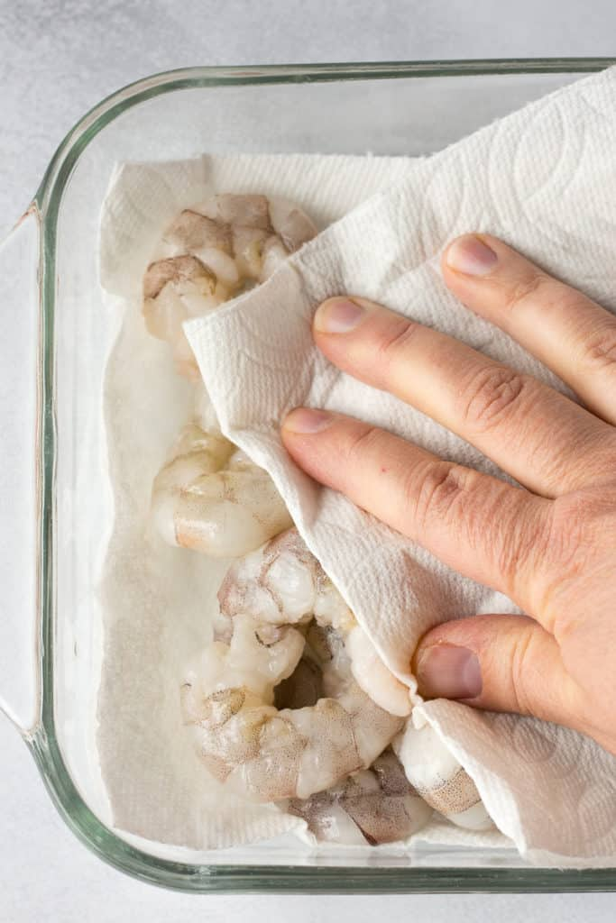 drying raw shrimp off with paper towels