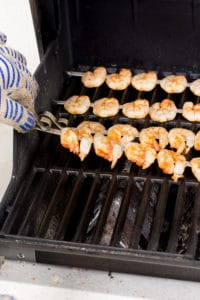 placing shrimp skewers on a gas grill with a hand in an oven mitt