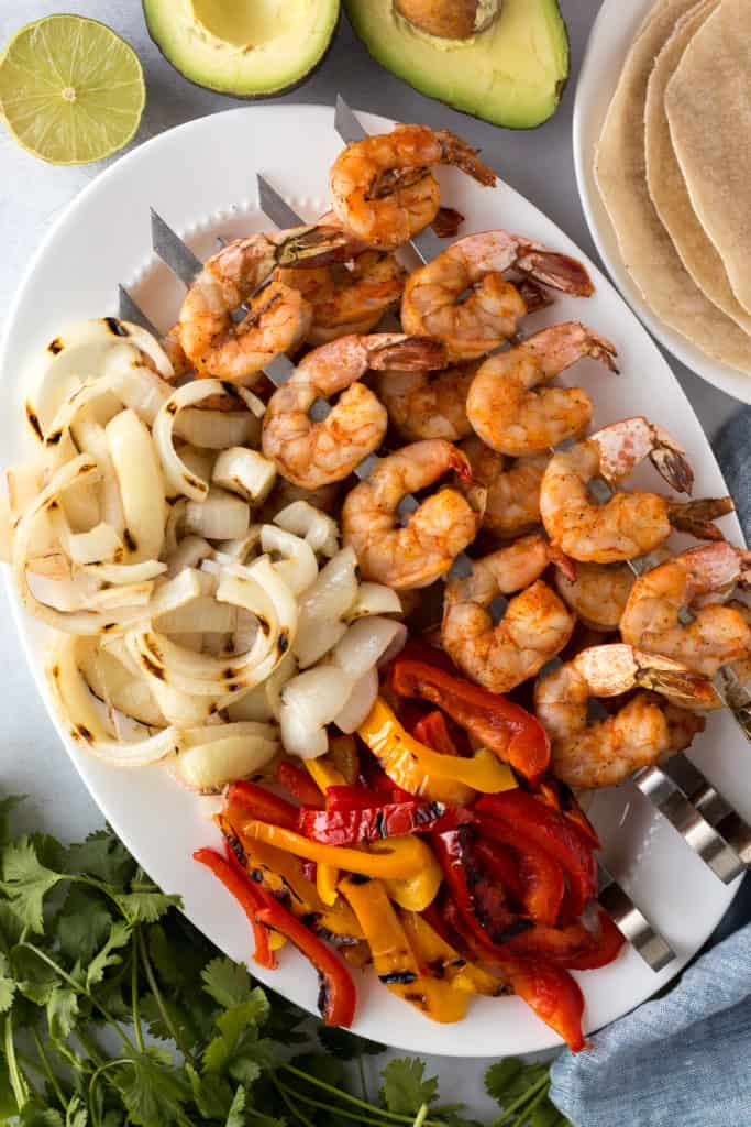 top down shot of a white platter with grilled shrimp on skewers, grilled onions and grilled bell peppers