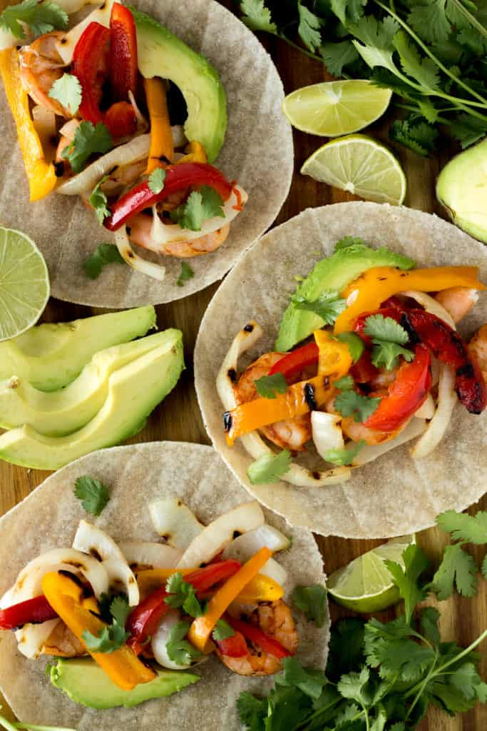 top down shot of three tortillas with shrimp fajitas in them and avocado and lime surrounding