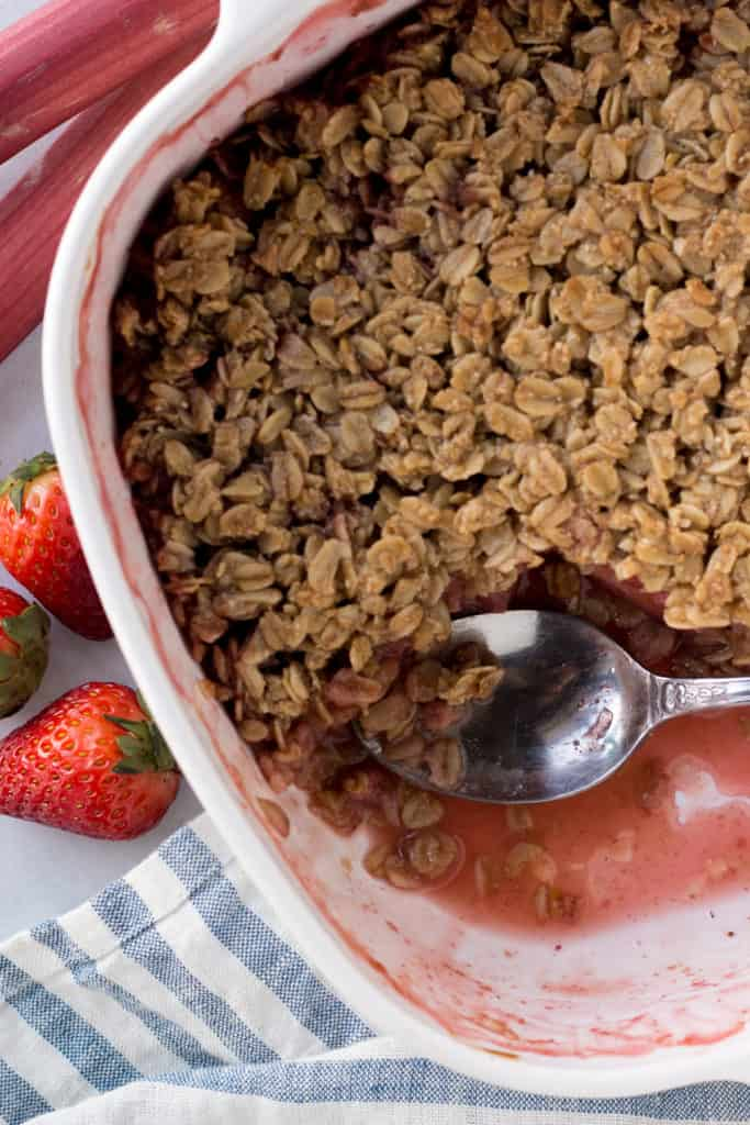 top down shot of gluten free strawberry rhubarb crisp in a bake dish with a spoon in it