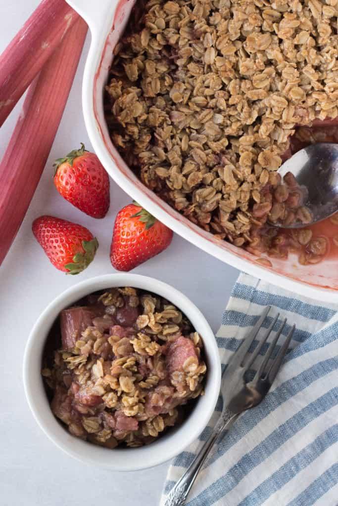 top down shot of a ramekin with strawberry rhubarb gluten free crisp next to a baking dish, strawberries, and rhubarb