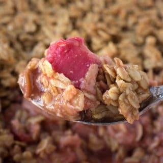 a close up shot of a spoonful of gluten free strawberry rhubarb crisp