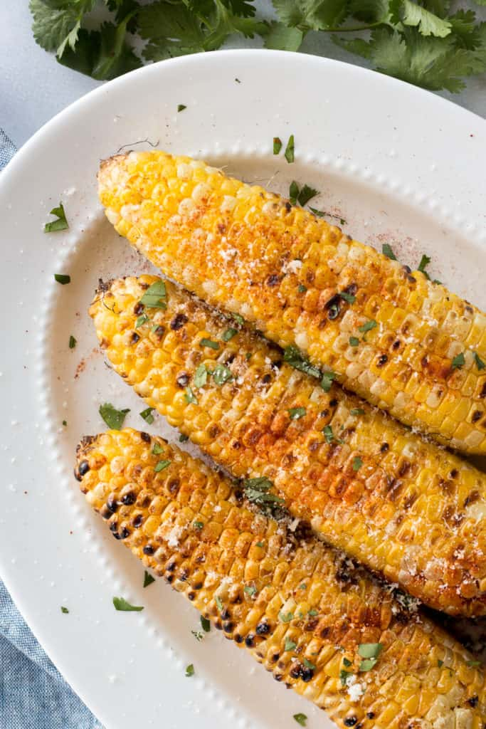 top down shot of grilled corn on the cob with toppings on a white platter