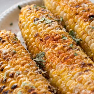 grilled sweet corn with paprika, parmesan, butter, and chopped cilantro on it