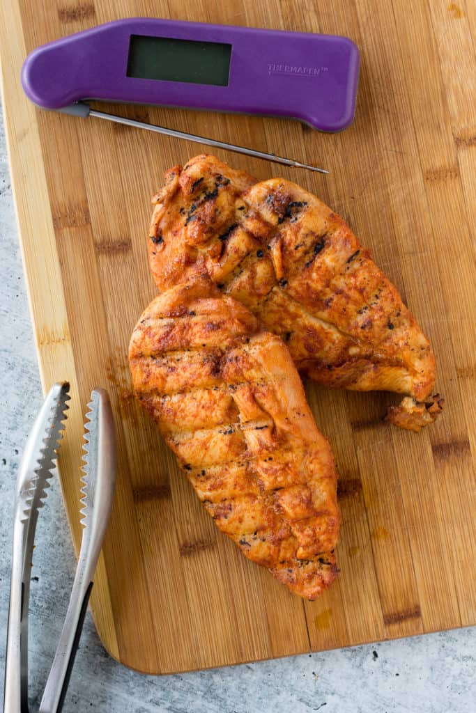 two smoked chicken breasts on a wood cutting board with tongs and a purple meat thermometer