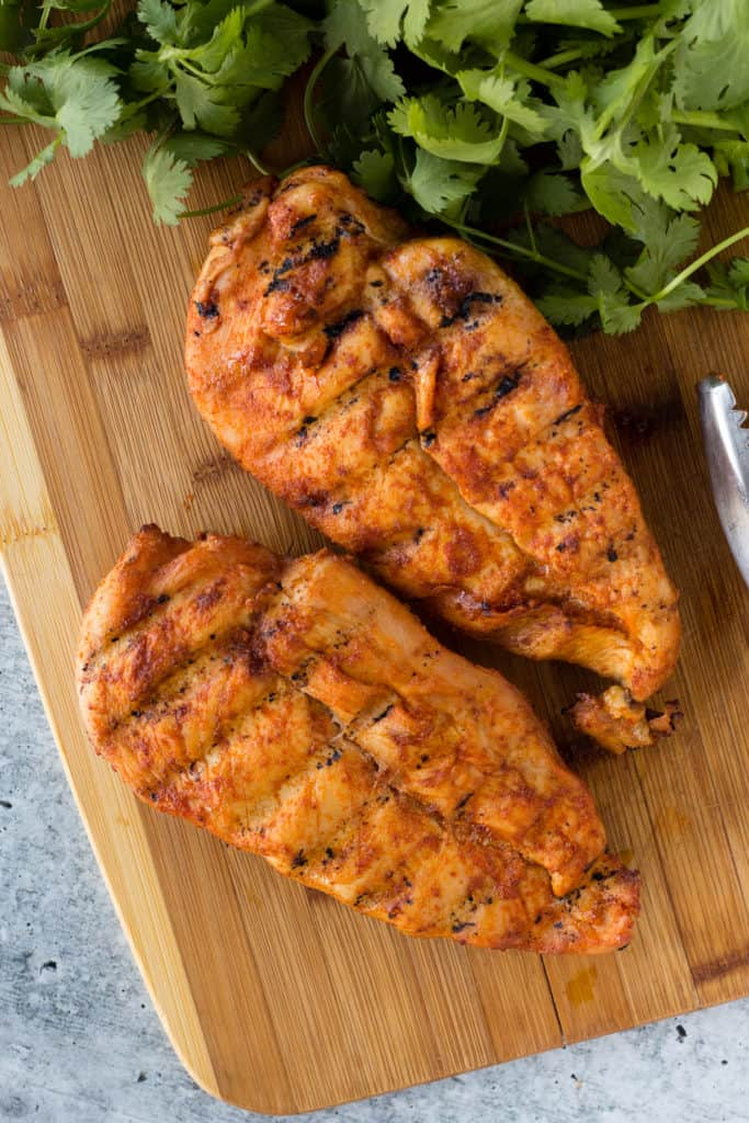 top down shot of two smoked chicken breasts on a cutting board next to cilantro