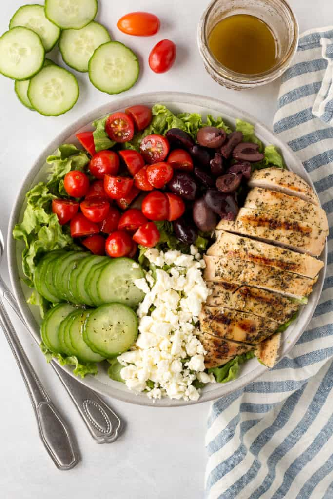top down shot of a large bowl of grilled chicken greek salad with silverware and accompaniments and napkin next to it.