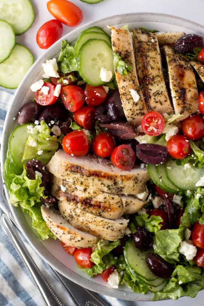 close up of greek chicken salad in a gray bowl with veggies and napkin on the side
