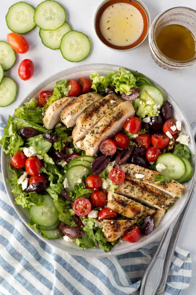 top down shot of greek salad with grilled chicken with a striped blue and white napkin and veggies to the side.