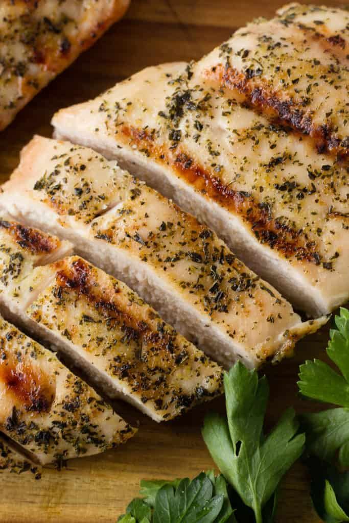 close up shot of sliced greek grilled chicken on a cutting board with parsley next to it