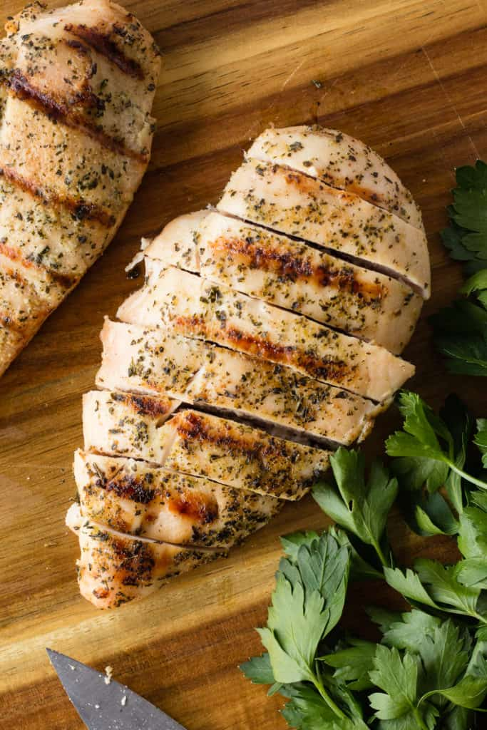 top down shot of greek grilled chicken breast on a cutting board with parsley and a knife