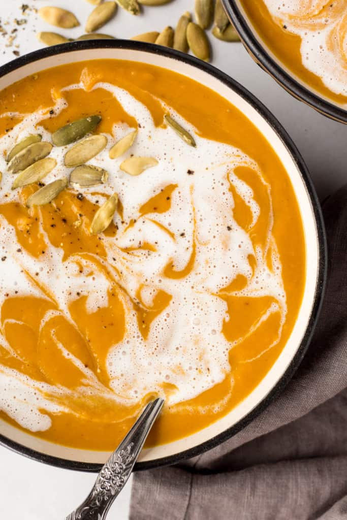 close up of sweet potato pumpkin soup in a bowl bowl with a spoon in it