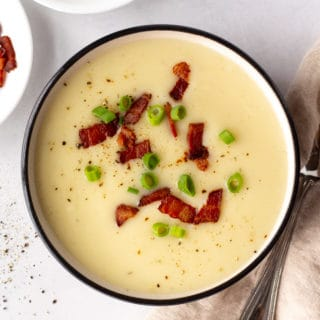 top down shot of a bowl of gluten free potato soup next to a tan napkin, a silver spoon, and two small white plates, one with green onion and the other with cooked bacon bits.