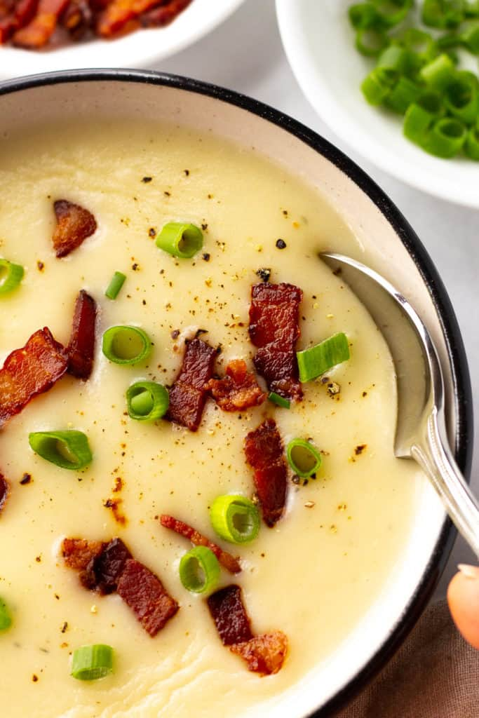 close up shot of a silver spoon dipping into a bowl of gluten free potato soup next to white bowls with bacon and green onion in them.